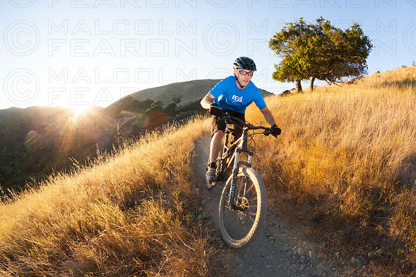 solo man riding downhill trail on mountain bike late evening sunset