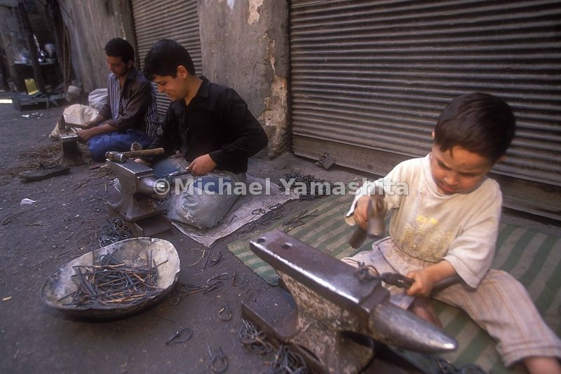 Young boys hammer out chain links to help make money. Baghdad
