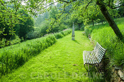 Grassy walk through the new orchard, with stone obelisk and bench. The Old Rectory, Netherbury, Dorset, UK