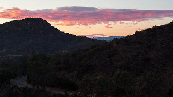 Medium Shot: A Dreamlike Sunset Of Pastel Clouds and Rolling Peaks