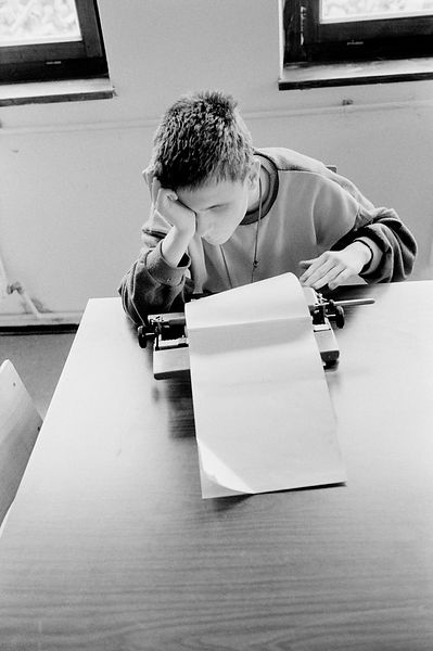 A boy types at the Blind School
