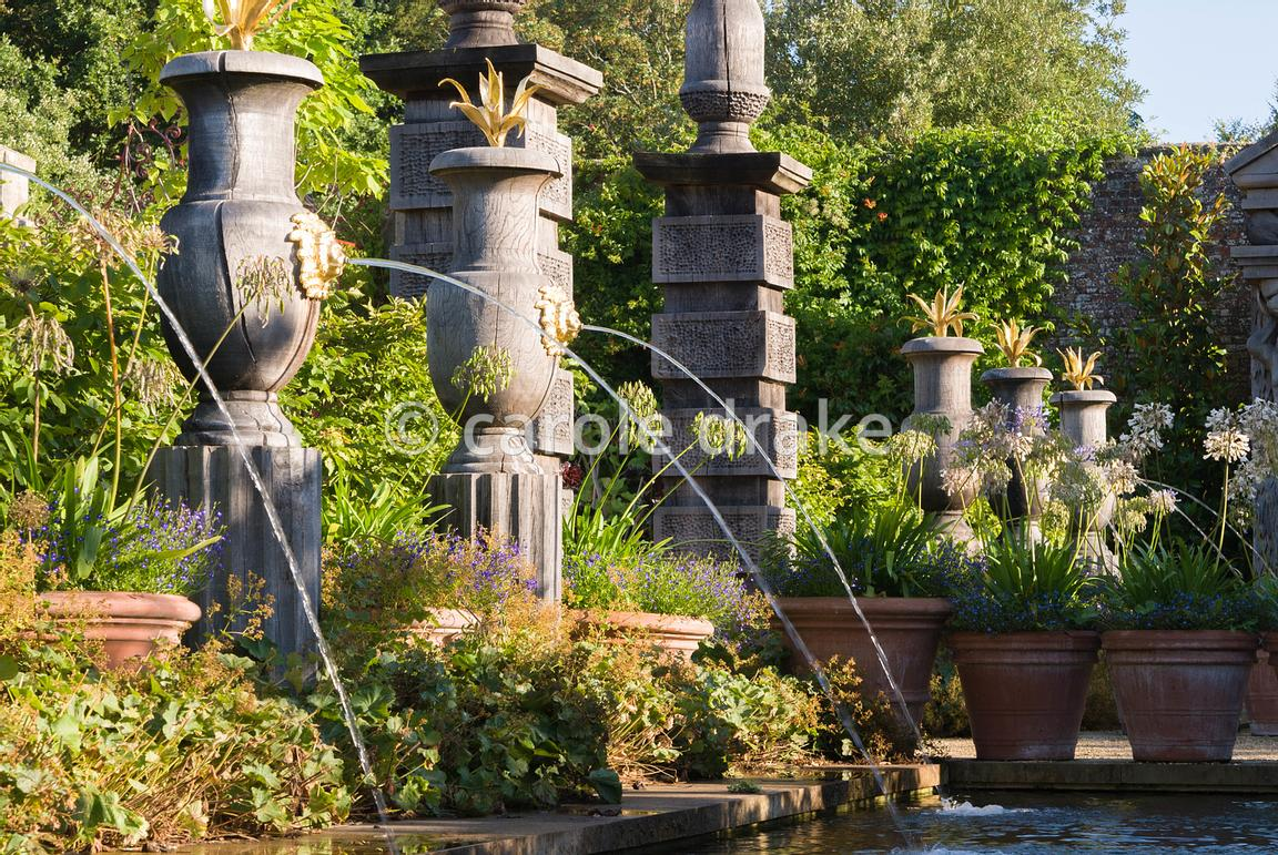 Rill pool flanked by turned oak urns spouting water through gilded lions' heads, with golden agaves in their tops. Planting includes Alchemilla mollis and white agapanthus. The Collector Earl's Garden designed by Julian and Isabel Bannerman. Arundel Castle Gardens, Arundel, West Sussex, UK