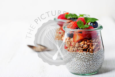 Сhia seeds vanilla pudding and berries on wooden rustic background