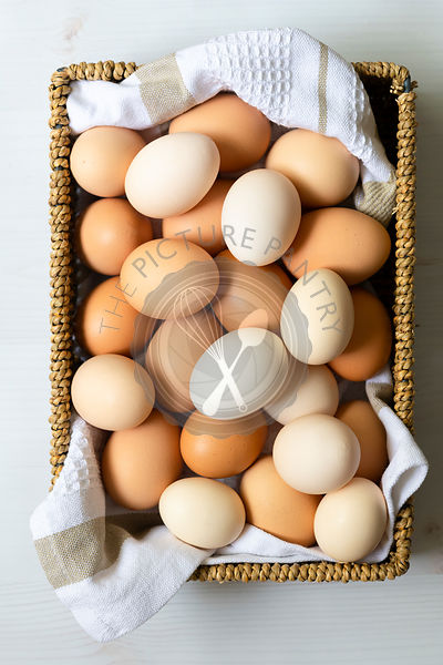 Brown and white eggs in a wicker basket.
