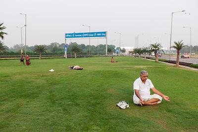India - New Delhi - A man meditates on the private traffic greens at Aerocity near Terminal 3 of Indira Gandhi Airport