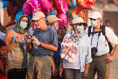 Foreign tourists cover their faces due to the air pollution from dust and smoke at the Pushkar Camel Fair, Pushkar, Rajasthan, India