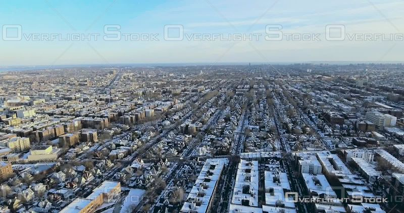 Aerial Crane Down Over Snow Covered Football Fields and Brooklyn Brownstones and Buildings Winter NYC