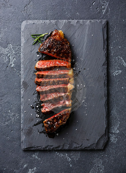 Sliced medium rare grilled Striploin steak on slate board