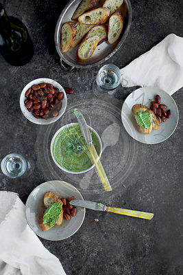 Arugula Chive Basil Pesto served in a ceramic bowl with crostini, almonds and wine.