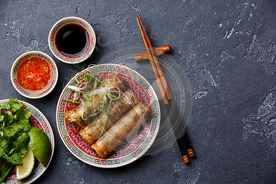 Spring rolls with sauce on black stone background copy space