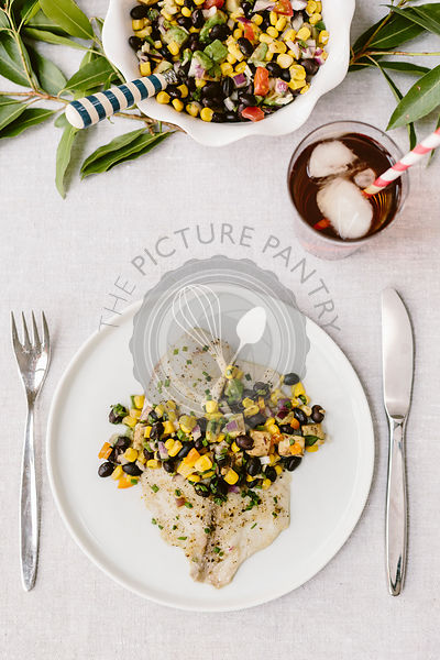 Two plates of Freshly baked tilapia topped off with black bean salsa are photographed on a summery tablesetting.