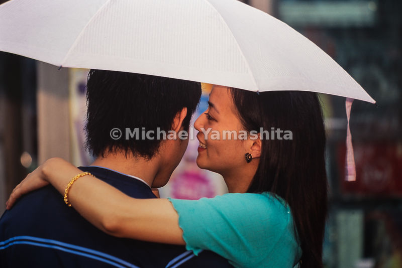 Young couple walks on the street with an umbrella in Shanghai, China.