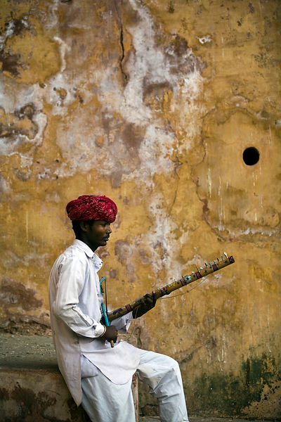 India - Rajasthan - A traditional Rajasthani gypsy musician tunes his Ravanhatta (violin) inside the Amber Fort