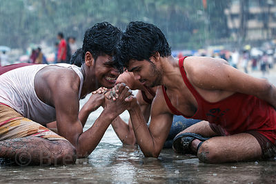A group of four men arm wrestle during monsoon rains at Juhu Beach, Mumbai, India.