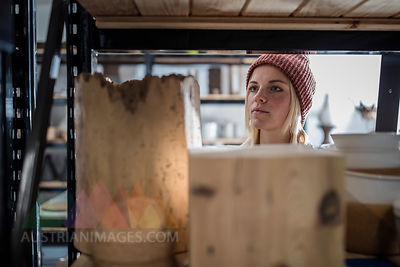Young woman in workshop looking at shelf