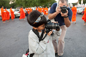 Tibetan buddhist monks near the Wat Benjamaborpit in Bangkok, Thailand are the backdrop for a very young photographer ironically being photographed by an American photographer.