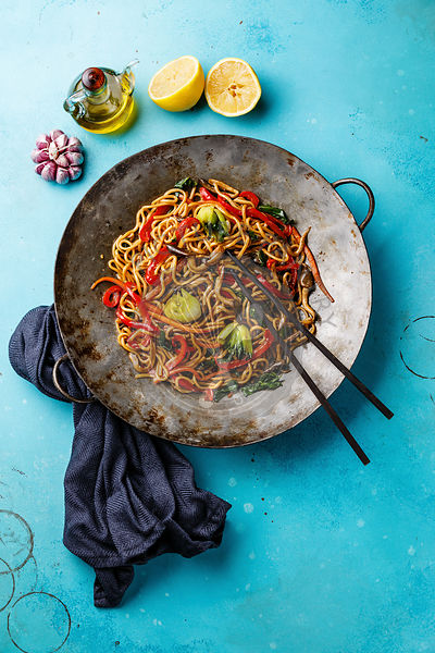 Udon stir fry noodles with oyster mushrooms and vegetables in wok pan on blue background