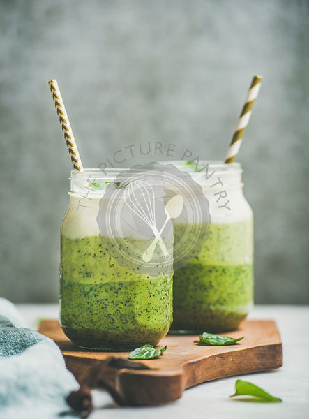 Ombre layered green smoothies with fresh mint and straws in glass jars, grey concrete wall background