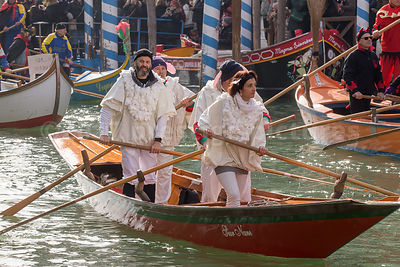 Men and Women wearing frilly White Costumes in a small Red Boat  in the Venice Carnival Water Parade