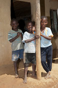 Happy children leaning on a post outside their home, Kenya.