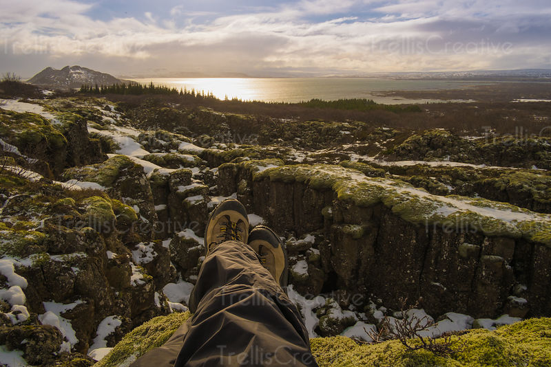 Mountain climber sits atop a mountain ledge with feet dangling off edge in Iceland
