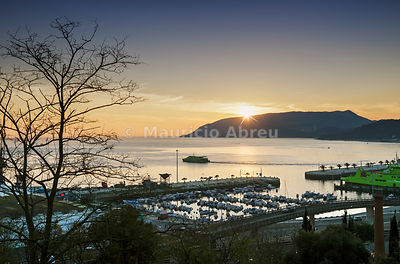Sunset at Setúbal and the Sado river with its bay, belonging to the UNESCO Club of the Most Beautiful Bays in the World. The Arrábida Nature Park in the background. Portugal