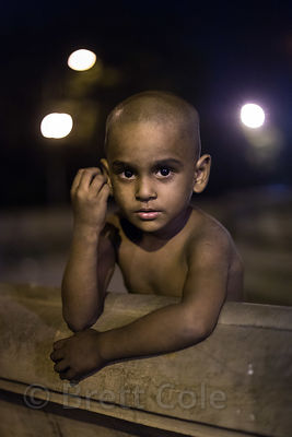 A small boy poses for a portrait at night, on a busy street with no parents anywhere in sight. He called me over and inisted I take his photo. BBD Bagh, Kolkata, India,
