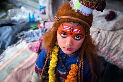 A boy in Kolkata, India dressed as Shiva receives baksheesk (donations) at a staging area for pilgrims going to the Gangasagar Mela on Sagar Island south of Kolkata.