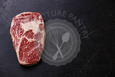 Raw fresh marbled meat Steak Rib eye Black Angus on dark background copy space
