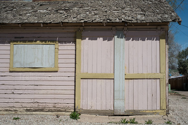 Weathered old garage exterior with doors on sliders