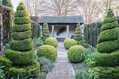 The Herb Garden with topiary box and yew and a summer house at the end. York Gate Garden, Adel, Leeds, Yorkshire