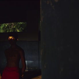 Arun, a student at the Kerala Kalamandalam stands in a shaft of light after practice. Kerala, India
