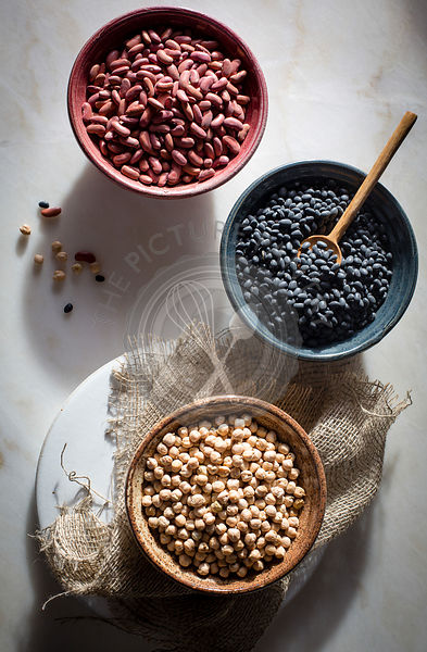 Garbanzo beans/chickpeas,kidney beans/rajma,black beans in individual ceramic bowls on a marble table on top view
