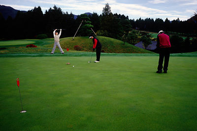 Japan - Hakone - a man stretches on a golf course