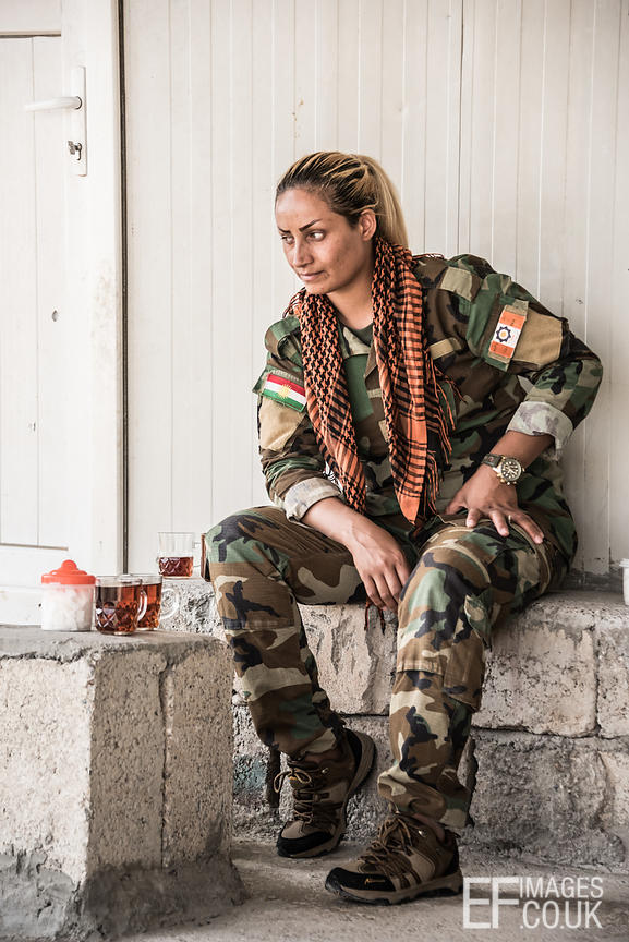 PAK (Kurdistan Freedom Party) female fighter taking a tea break at her base north of Hawija, where Kurdish Iranian fighters are holding the line against the last vestiges of Daesh and preparing to engage the Hashd al Shaabi forces threatening Kirkuk. Kirkuk Governorate, Iraq, 14th October 2017