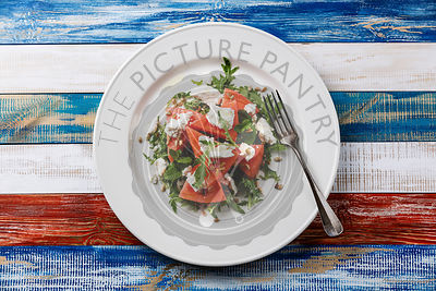 Watermelon salad with arugula, ricotta cheese and sunflower seed on wooden background