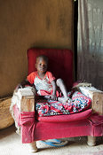 A young african child relaxing on a homemade armchair in his home. Kenya