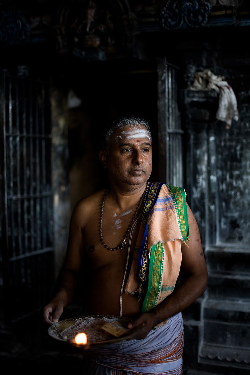 A priest by a shrine at the Murugan temple, gives ritual blessings to pilgrims in Swamimalai