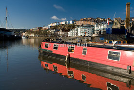 narrow boat on floating harbour with the coloured buildings of hotwells in the distance bristol england