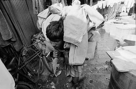 A Dhobi (or washerman) in Bombay (now Mumbai) carries washing to be delivered