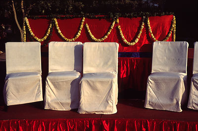 India - Delhi - A stage set for a wedding with chairs and garlands