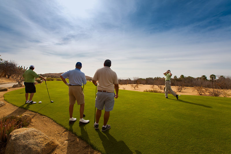 Three men watch a golfer teeing off on a luxury golf course in Mexico