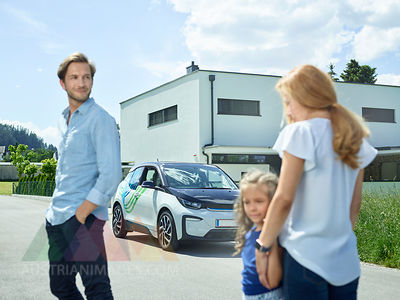 Family with electric car in front of house