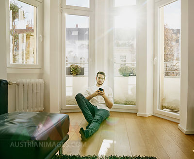 Man sitting on floor looking at cell phone