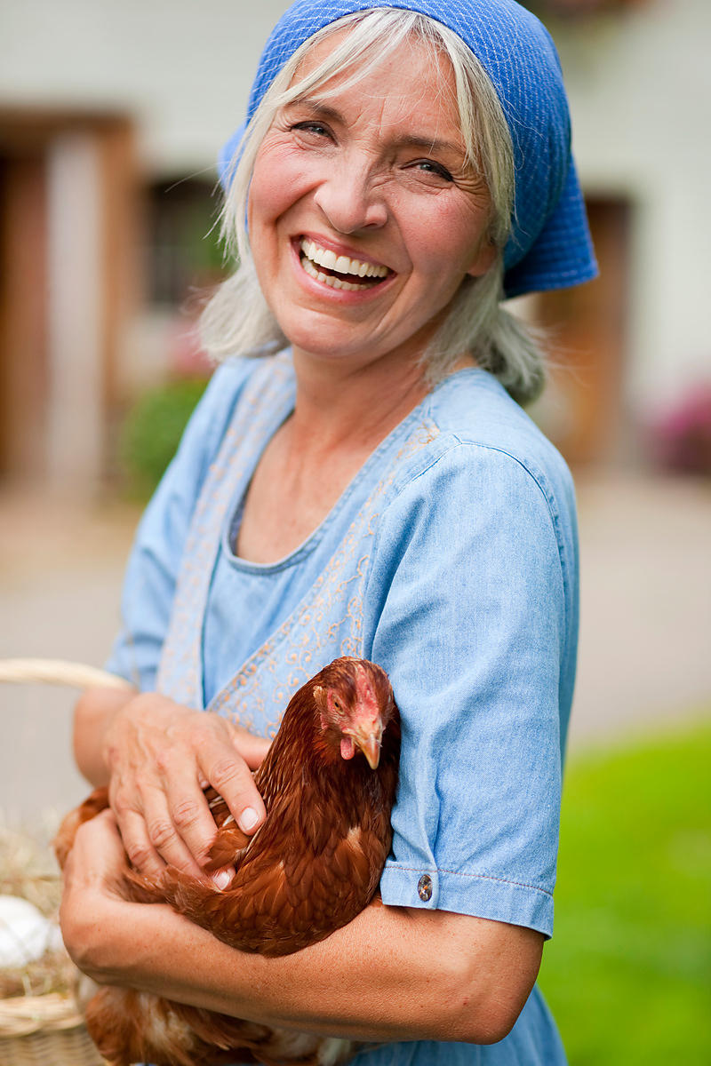 farm woman with basket of fresh eggs and chicken in front of farm, Memmingen, Bavaria, Germany