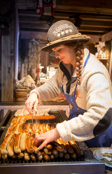 Young Woman cooking sausages at the Hamburg Christmas Market 2016