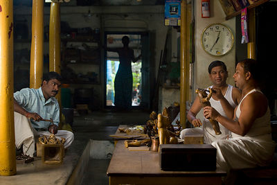 India - Swamimalai - Master craftsmen Radhakhrishna Stpathy (r) and his brorther, Srikanda mould an icon in wax in their workshop