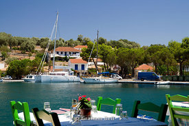 Yachts moored in Vathi Harbour from a waterfront Taverna, Meganisi, Lefkas, Ionian Islands, Greece.
