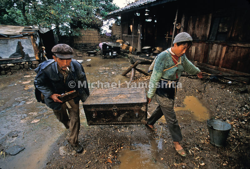 Heirs to generosity, Li Jinyuan and his wife carry a chest containing carpentry and dental tools given by Rock to Li's father, who had built furniture for Rock in Yuhu.