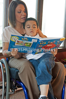 Young mother in a wheelchair reading a story book to her son